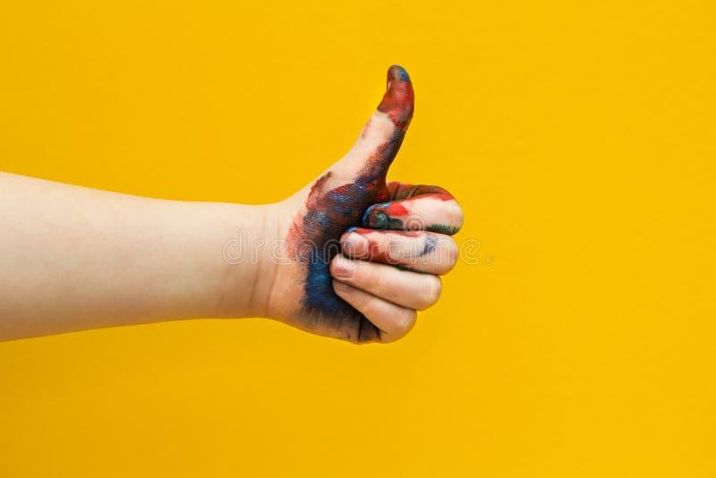 La mano dei bambini, spalmata di pittura multicolore su un fondo giallo Pollici in su fotografia stock libera da diritti