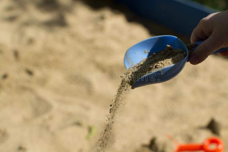 La mano dei bambini versa la sabbia con una pala blu fotografia stock libera da diritti