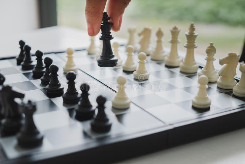 La mano del ajedrez de mudanza del hombre de negocios en la competencia, muestra la dirección, los seguidores y las estrategias d fotos de archivo
