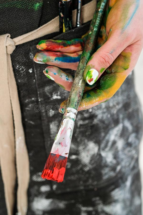La mano del artista de la mujer con un cepillo y una pintura roja Delantal negro, fondo blanco fotografía de archivo libre de regalías