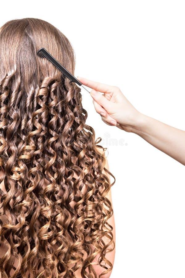 La mano del barbiere che pettina capelli ondulati lunghi isolati su bianco immagine stock libera da diritti