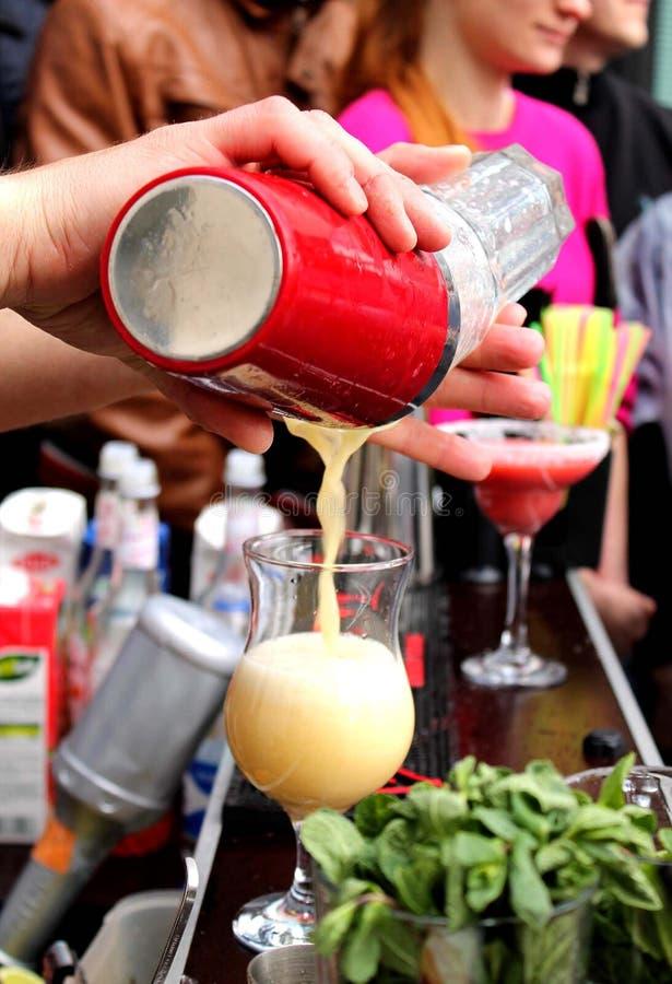 La mano del barista con il cocktail di versamento del miscelatore di scossa in vetro fotografia stock libera da diritti