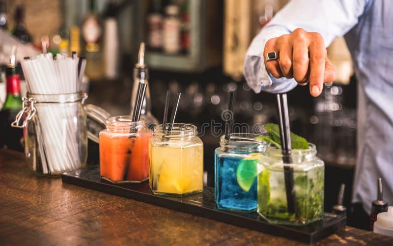 La mano del barista a modo multicolore beve alla barra del cocktail fotografia stock libera da diritti