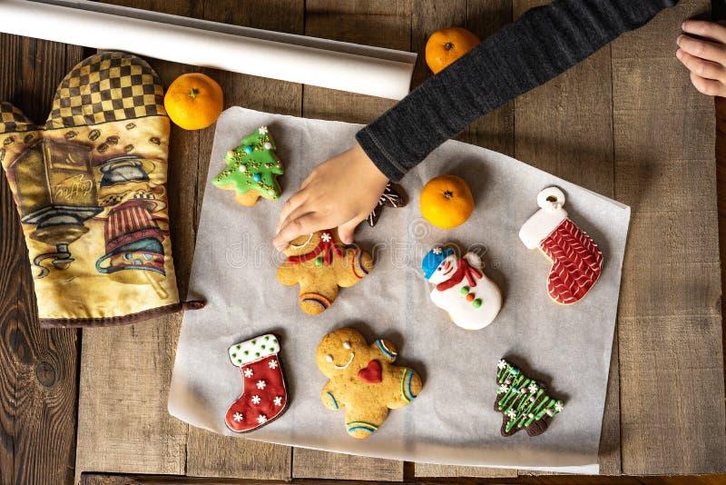 La mano del bebé coge el pan de jengibre de la tabla cooki del pan de jengibre foto de archivo