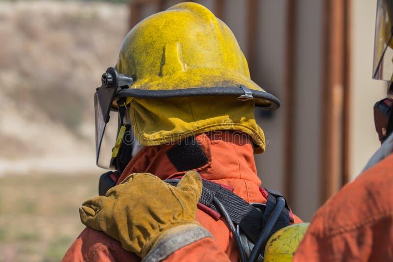 La mano del bombero puso el hombro del primer hombre para la señal en fuego fotos de archivo libres de regalías