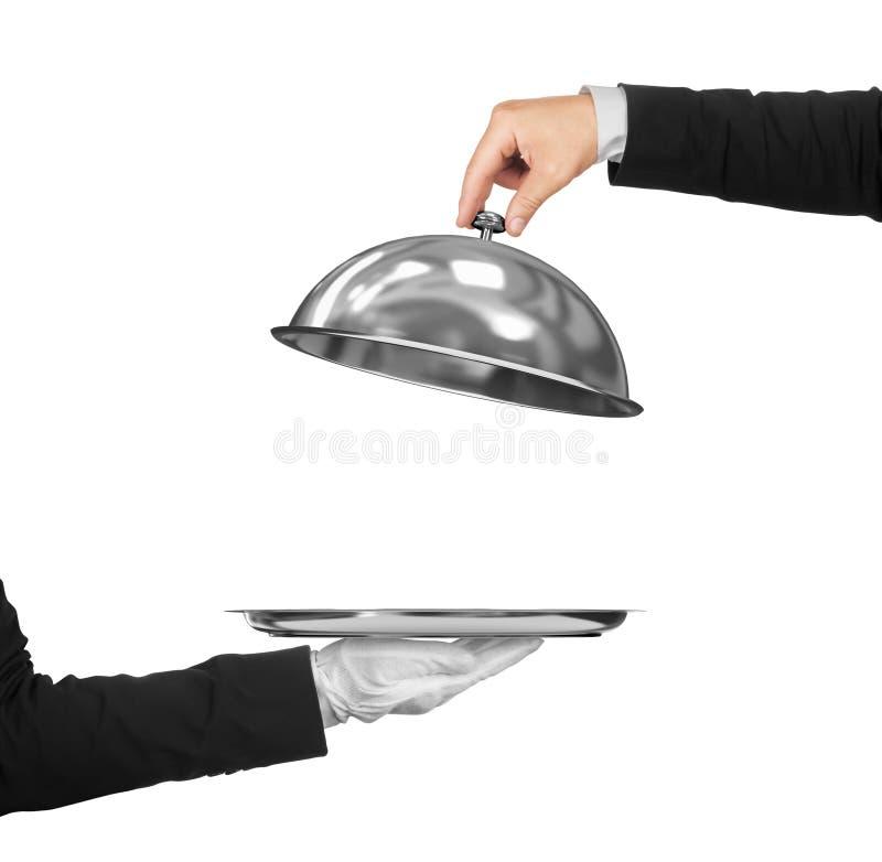 La mano del camarero que sostiene la campana de cristal sobre vacío foto de archivo
