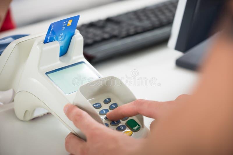 La mano del cliente que inscribe a Pin Code On Card Reader imagenes de archivo