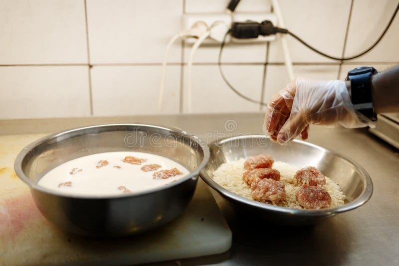 La mano del cocinero cocina las chuletas en empanar fotos de archivo