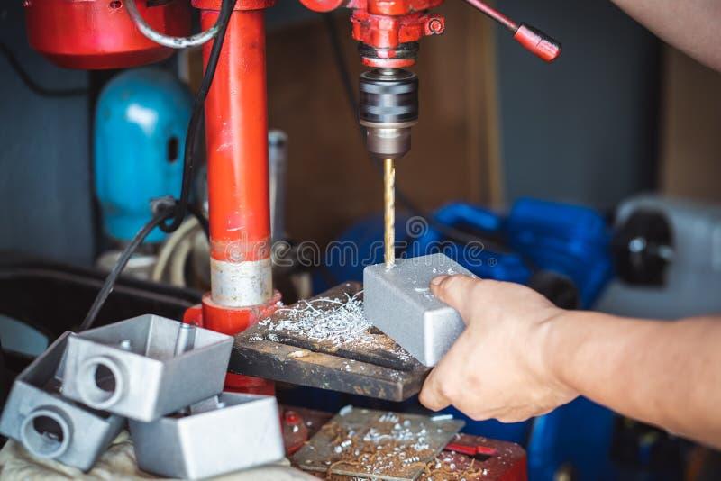 La mano del contenitore di metallo della tenuta dell'uomo del lavoratore e del foro è perforata, Th fotografia stock libera da diritti