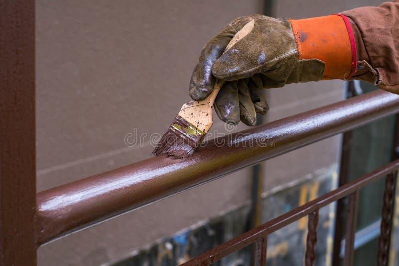 La mano del contratista con el cepillo que construcción que cerca con barandilla del metal de la pintura imagen de archivo