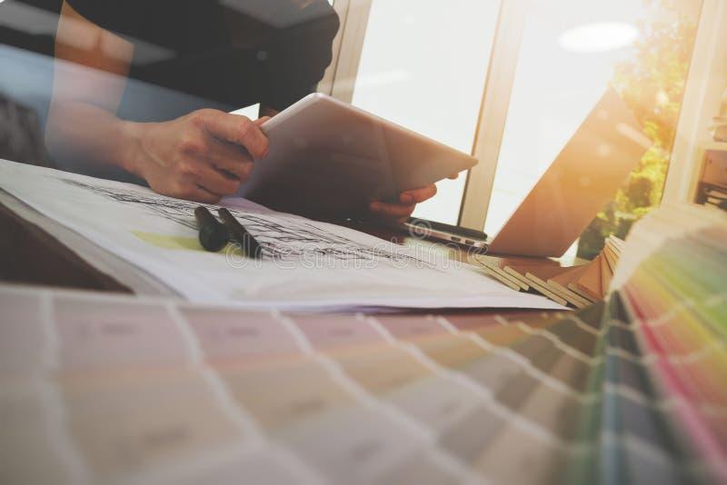 La mano del diseñador que trabaja con el ordenador portátil y el smarth llaman por teléfono fotografía de archivo libre de regalías