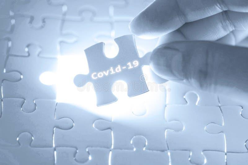 La mano del dottore con un puzzle con parole Covid-19 Concetto di salute Interrompi focolaio di Novel Coronavirus covid-19 2019-n fotografie stock