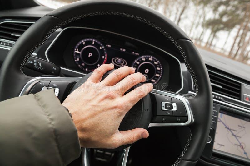 La mano del driver spinge un clacson del volante fotografie stock