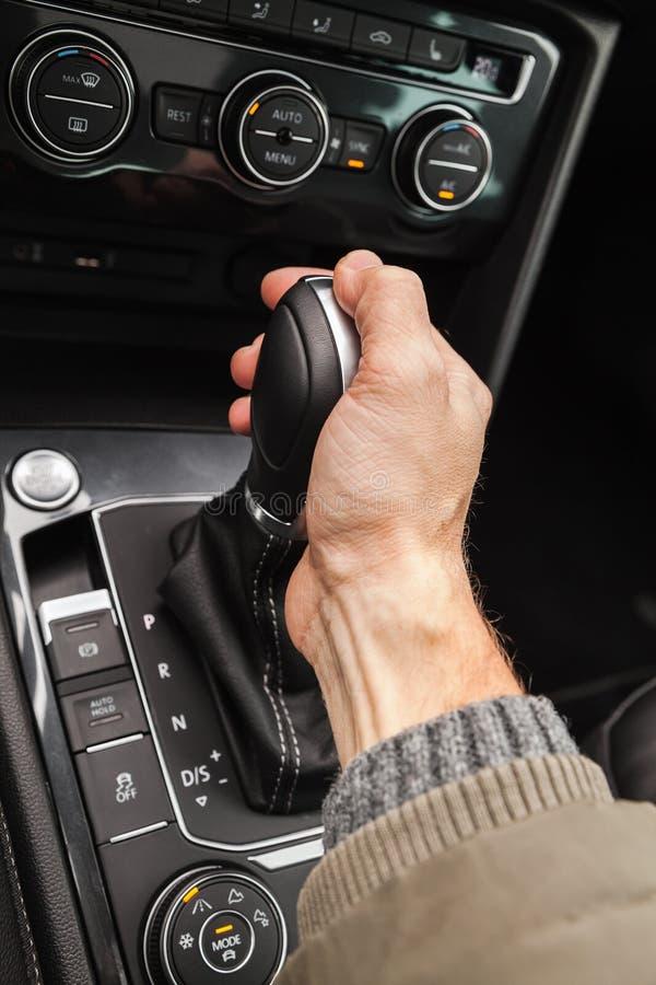 La mano del driver tiene il cambio fotografia stock