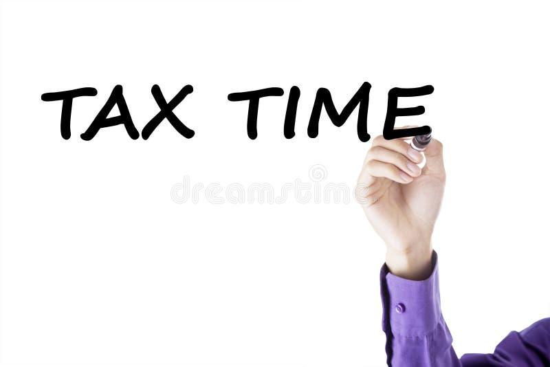 La mano del empresario escribe tiempo del impuesto foto de archivo
