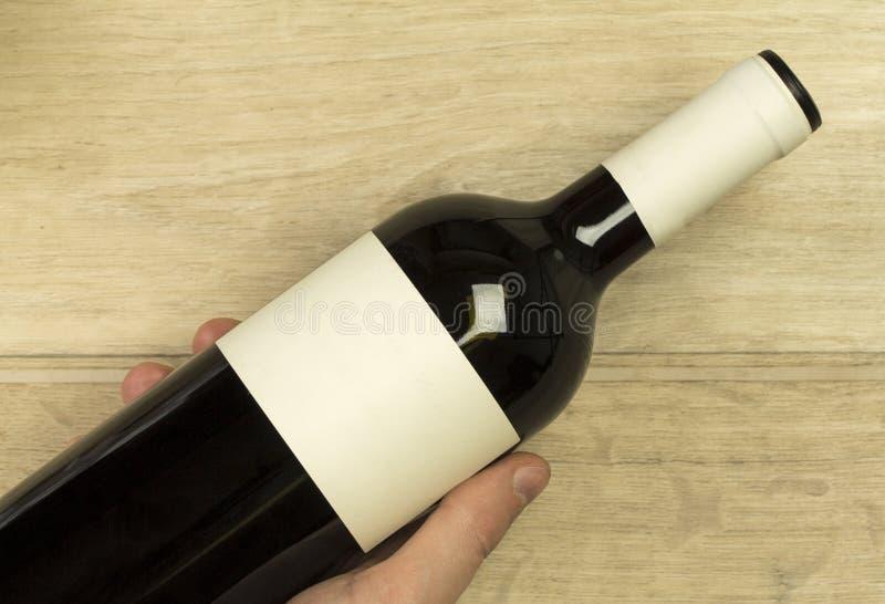 La mano del giovane sta tenendo la bottiglia del vino rosso ai precedenti di legno leggeri immagini stock libere da diritti