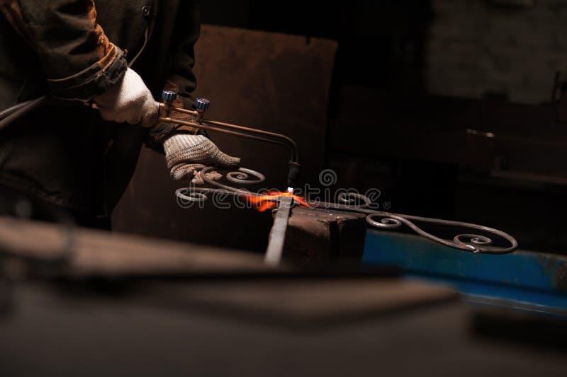 La mano del herrero en guantes protectores suelda un metal fotografía de archivo