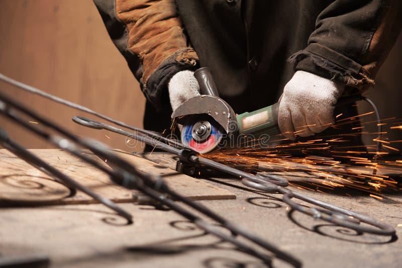 La mano del herrero en guantes protectores suelda un metal foto de archivo libre de regalías