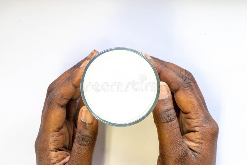 La mano del hombre africano que sostiene el vidrio de leche fresca caliente en el fondo blanco Comida y bebida de la visión super imagenes de archivo