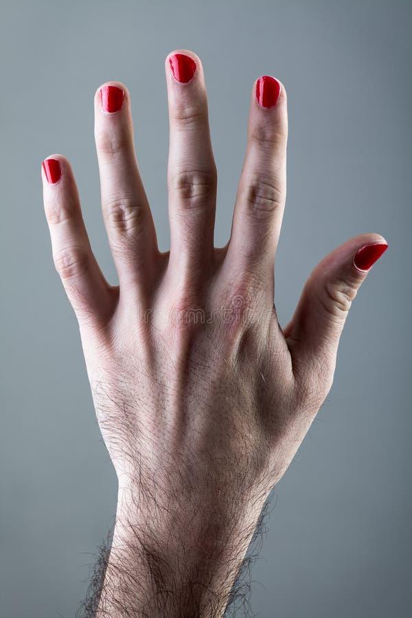La Mano Del Hombre Con El Esmalte De Uñas Rojo Imagen de archivo ...