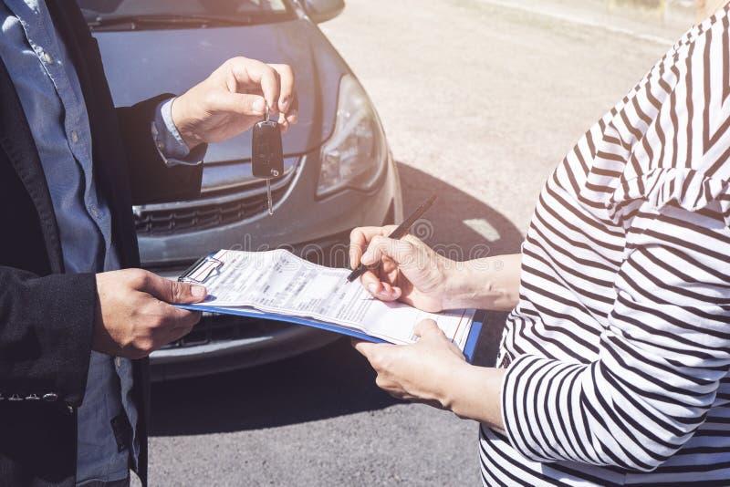 La mano del hombre de negocios da la llave del coche fotografía de archivo