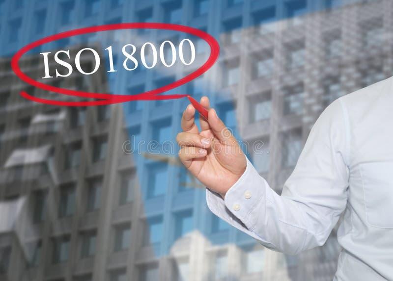 La mano del hombre de negocios joven escribe la palabra ISO 18000 en rascacielos foto de archivo libre de regalías