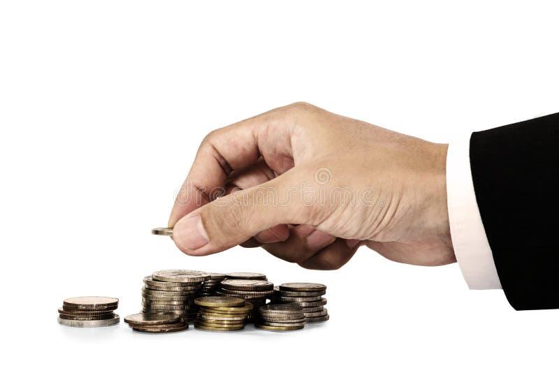 La mano del hombre de negocios que pone el dinero acuña, ahorrando el concepto del dinero, aislado en el fondo blanco imagen de archivo libre de regalías