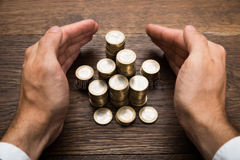 La mano del hombre de negocios que protege monedas euro fotografía de archivo