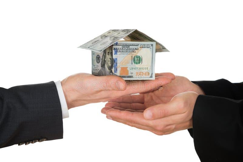 La mano del hombre de negocios que sostiene la casa hecha de dólar americano imágenes de archivo libres de regalías