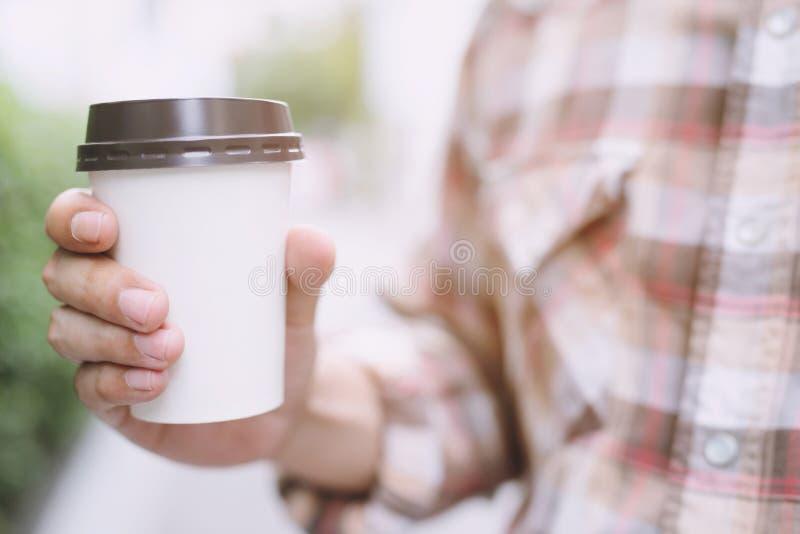 La mano del hombre de negocios que sostiene la taza de papel de se lleva el café de consumición en natural foto de archivo