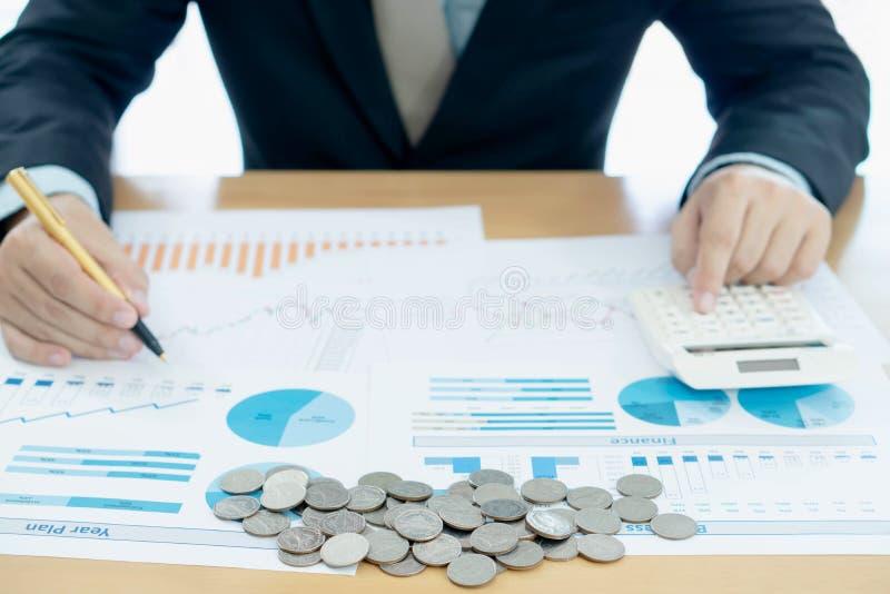 La mano del hombre de negocios usando la calculadora y los informes documentan la fabricación de cuenta financiera foto de archivo