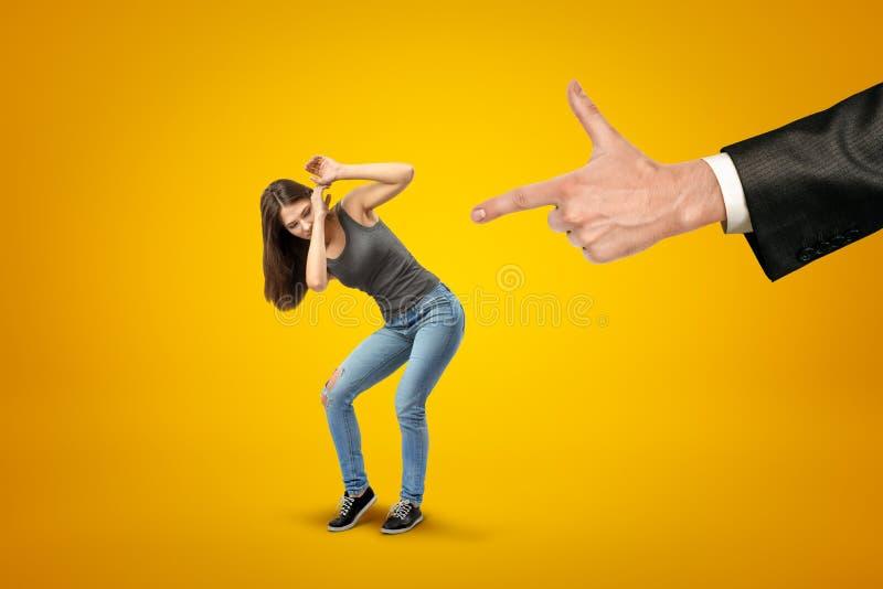 La mano del hombre en el traje que señala el fingergun en la muchacha bonita miniatured en ropa casual, que está protegiendo su c fotografía de archivo libre de regalías
