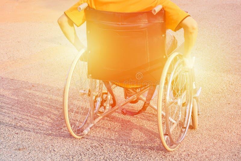 La mano del hombre en la rueda de la silla de ruedas en el camino en el parque de la ciudad nos utiliza tono caliente de la incap fotos de archivo