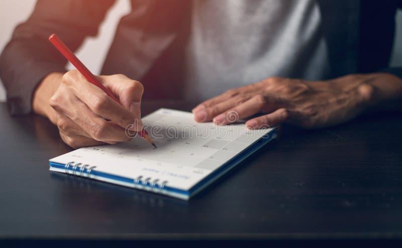 La mano del hombre es escribe una nota en un calendario fotos de archivo libres de regalías