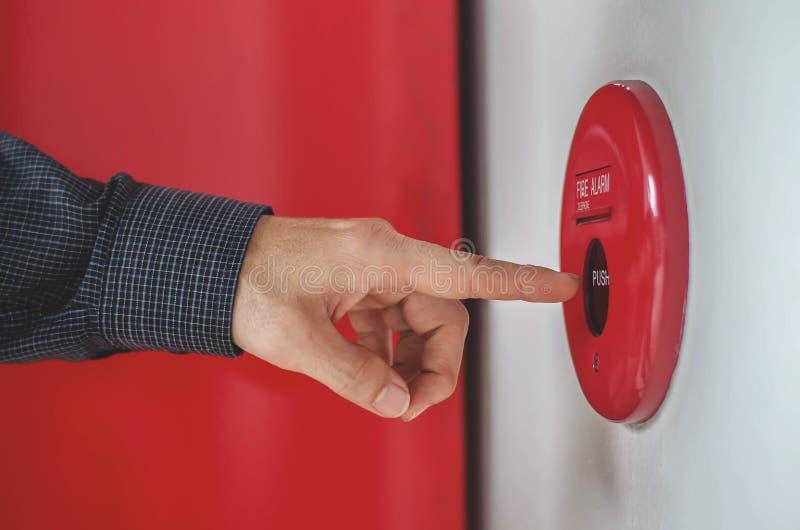 La mano del hombre es interruptor la alarma de incendio de la prensa en la pared blanca como fondo para el caso de emergencia en  imágenes de archivo libres de regalías