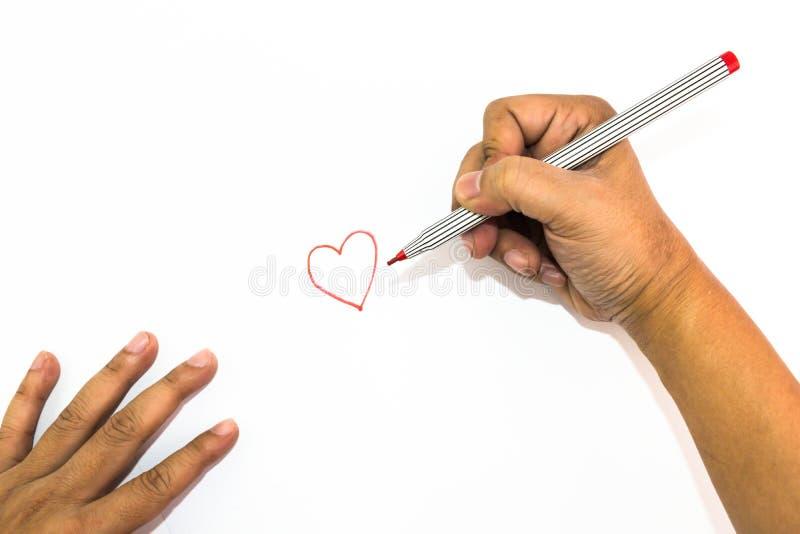 La mano del hombre está dibujando la muestra del corazón con el rotulador rojo imágenes de archivo libres de regalías