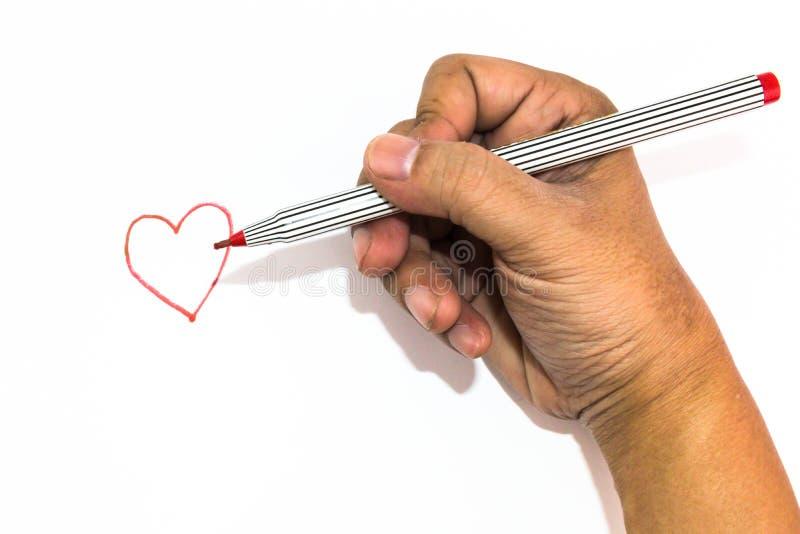 La mano del hombre está dibujando la muestra del corazón con el rotulador rojo fotos de archivo