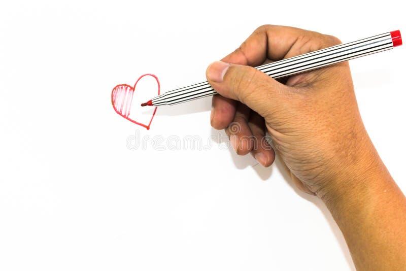 La mano del hombre está dibujando la muestra del corazón con el rotulador rojo foto de archivo libre de regalías