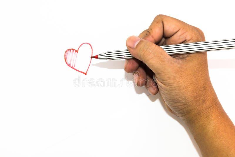 La mano del hombre está dibujando la muestra del corazón con el rotulador rojo imagenes de archivo