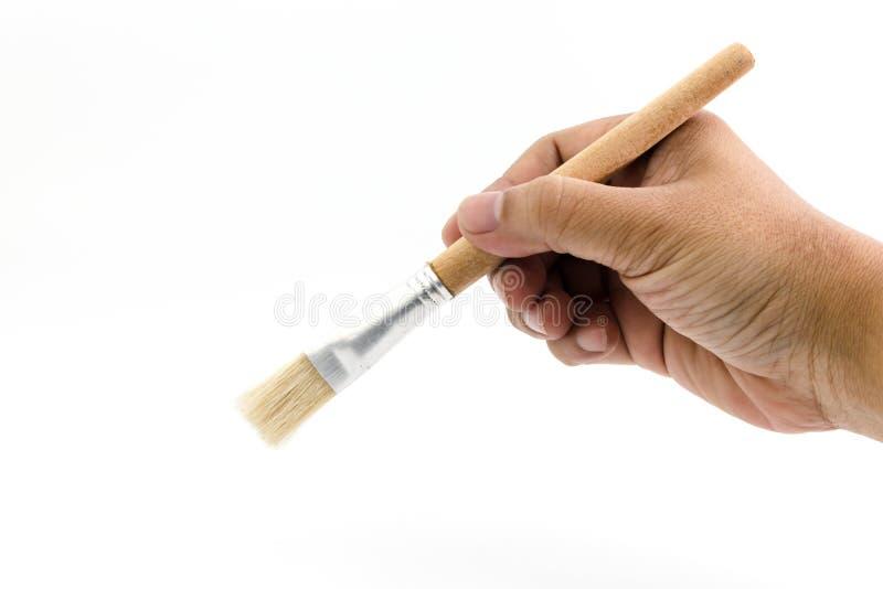 La mano del hombre está sosteniendo el cepillo de madera del dibujo aislado fotos de archivo