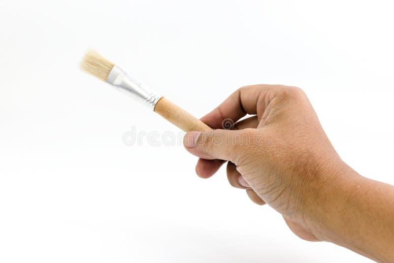 La mano del hombre está sosteniendo el cepillo de madera del dibujo aislado fotografía de archivo libre de regalías