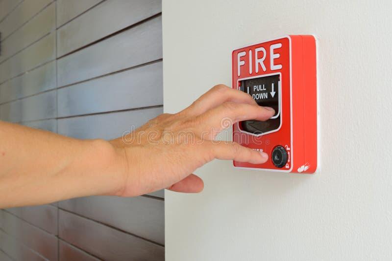 La mano del hombre está tirando de la alarma de incendio imagen de archivo