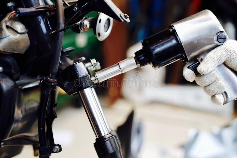 La mano del hombre del mecánico substituye y ajusta el sistema del freno trasero de la motocicleta imagenes de archivo