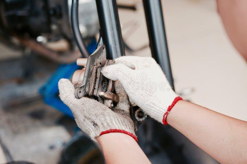 La mano del hombre del mecánico substituye y ajusta el sistema del freno trasero de la motocicleta imagen de archivo libre de regalías