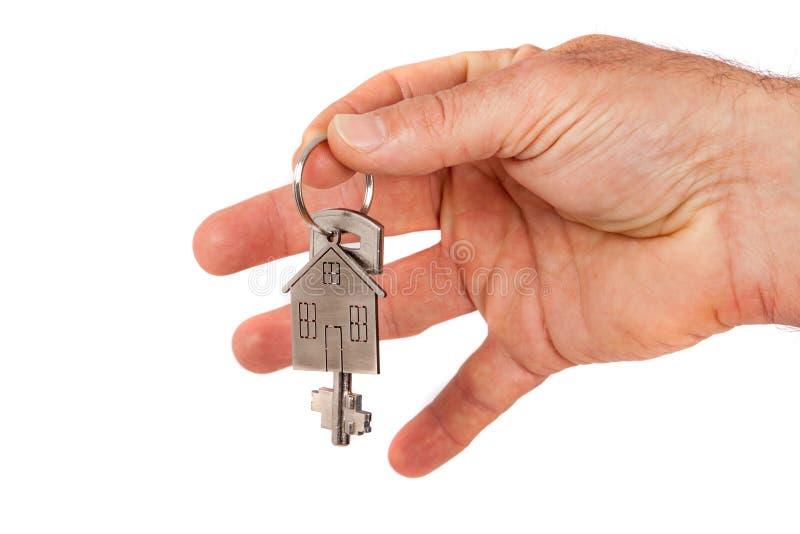 La mano del hombre que da una nueva llave del metal con el llavero formado casero, aislado Nuevo concepto casero foto de archivo libre de regalías
