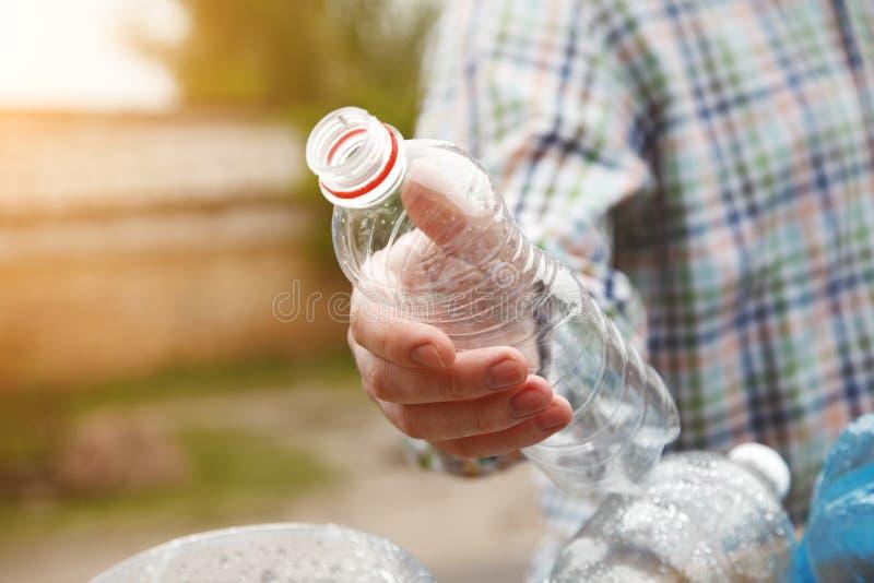 La mano del hombre que lanza la botella plástica reciclable transparente clara en compartimiento de basura imagenes de archivo