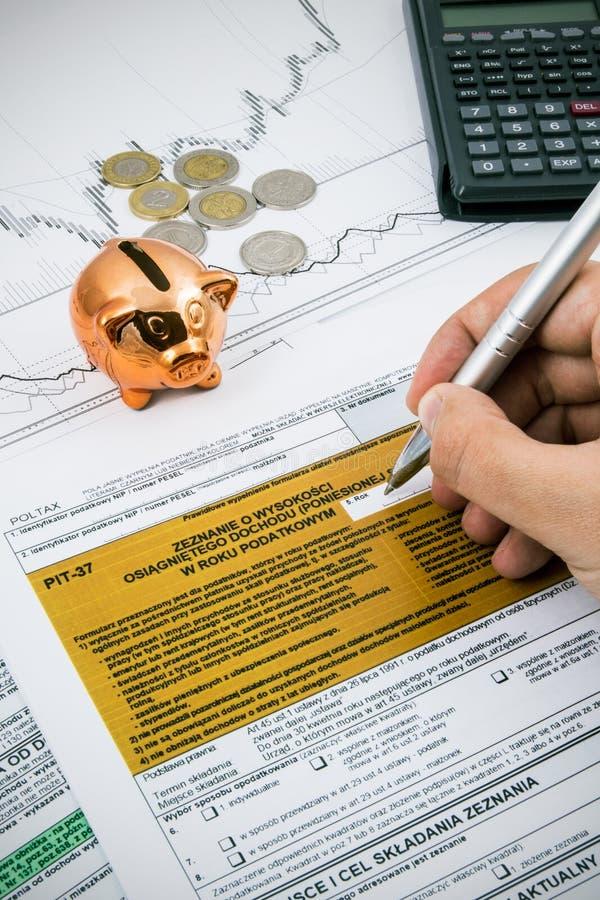La mano del hombre que llena impuesto sobre la renta polaco PIT-37 forma imagen de archivo libre de regalías
