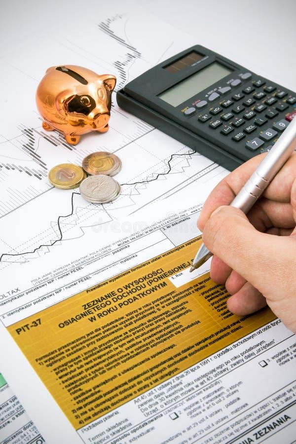 La mano del hombre que llena impuesto sobre la renta polaco PIT-37 forma foto de archivo libre de regalías
