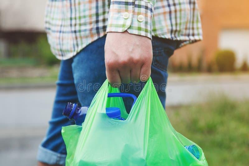 La mano del hombre que lleva la bolsa de plástico verde por completo de botellas plásticas listas para reciclar, espacio de la co fotos de archivo libres de regalías