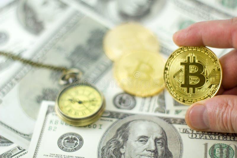 La mano del hombre que lleva a cabo el bitcoin de oro sobre el fondo de dólares americanos fotos de archivo